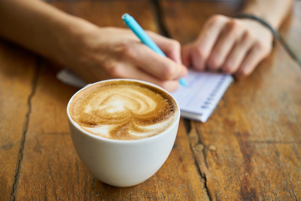cup of coffee and a hand shown writing in a notebook